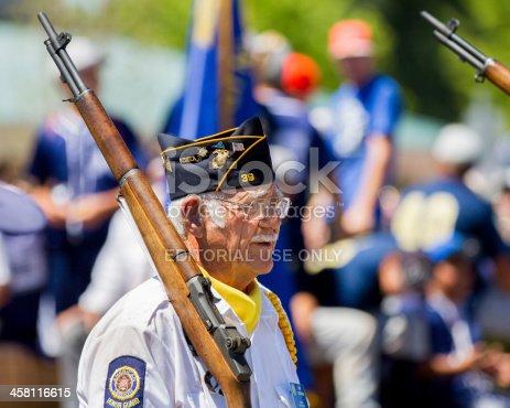 istock Man walking during a parade holding his gun 458116615