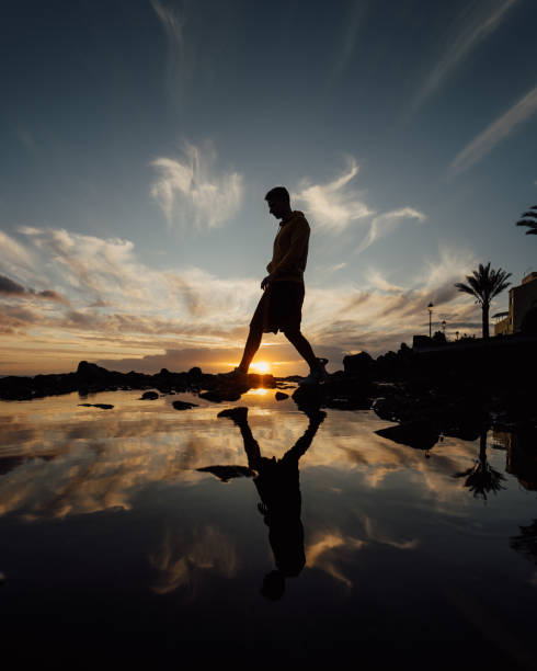 Man walking during sunset at seaside, La Palma, Canary Islands, Spain stock photo