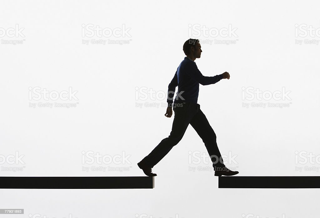 Man walking from a plank onto another plank stock photo