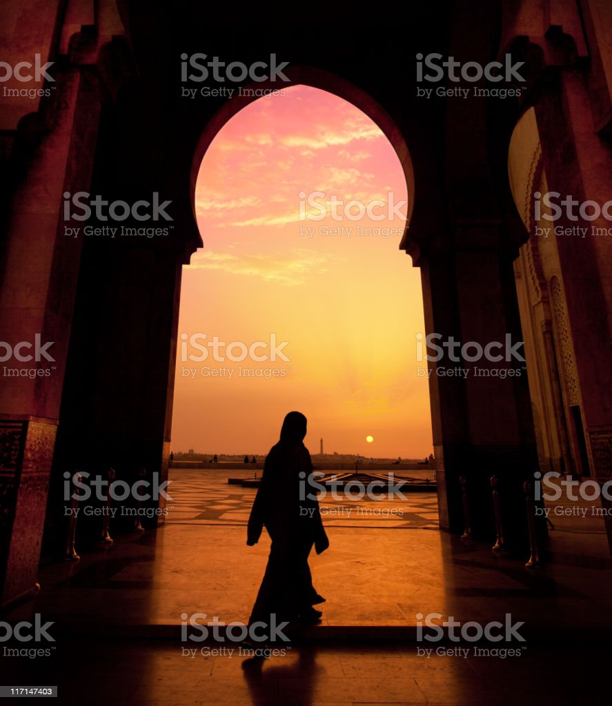 A man walking in a mosque during a sunset stock photo