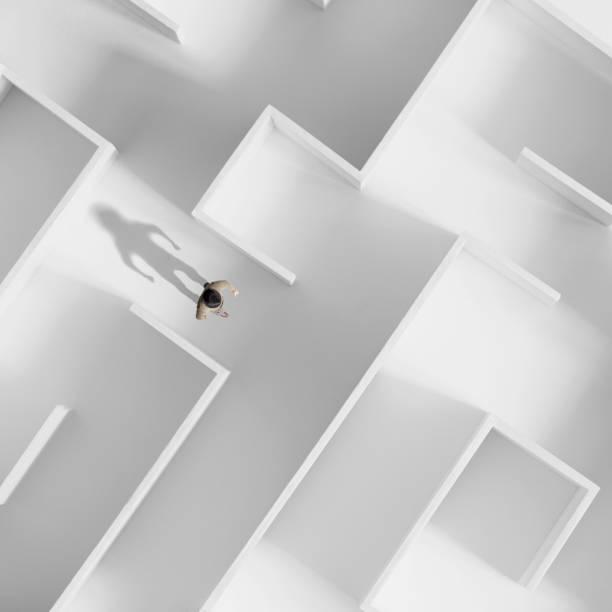 man walking in a white labyrinth, philosophical concept - intrappolato foto e immagini stock