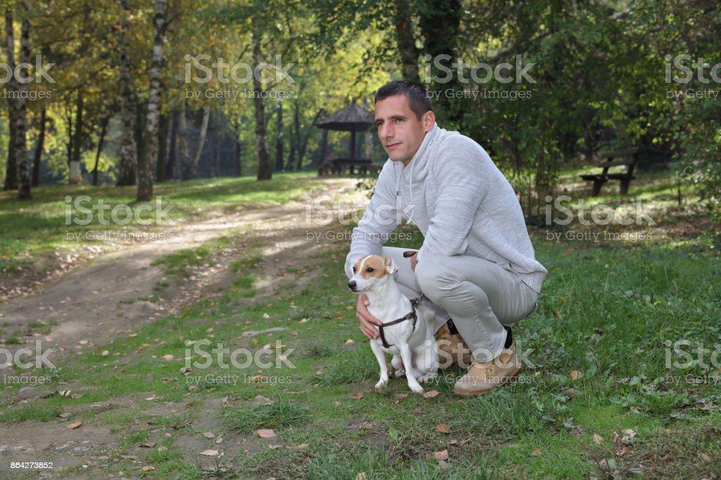 Man walking in autumn colorful forest with dog jack russell terrier royalty-free stock photo