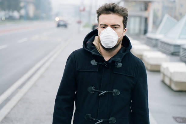 Man walking in city wearing mask against smog air pollution Man wearing protection mask against traffic smog air respiratory disease stock pictures, royalty-free photos & images