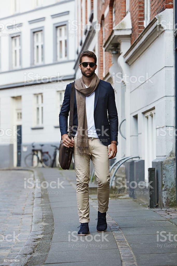 Man walking in city wearing sunglasses and scarf Lizenzfreies stock-foto