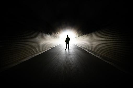 Man walking in dark tunnel