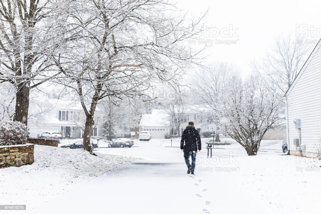 Man Walking In Driveway In Neighborhood With Snow Covered