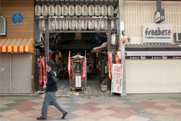 A Man Walking in front of a Temple inside a Shopping Arcade