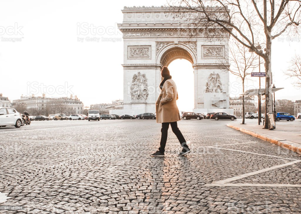 Man walking in front of Arc de Triomphe stock photo