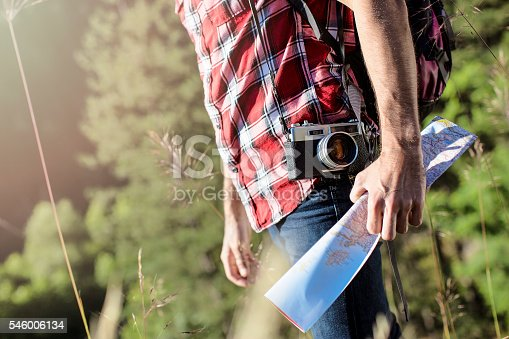istock Man walking in nature with camera and map 546006134