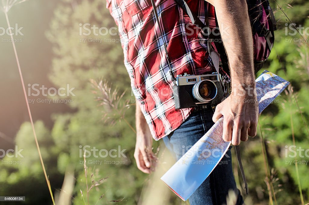 Man walking in nature with camera and map ストックフォト