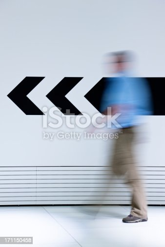 istock Man walking in opposite direction of arrow 171150458