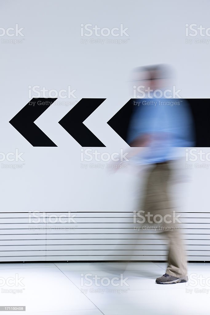 Man walking in opposite direction of arrow stock photo