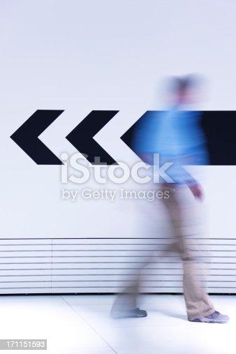 171150458istockphoto Man walking in opposite direction of arrow 171151593