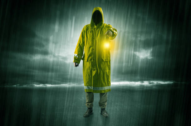 Man walking in storm with lantern Raincoated man walking in storm with glowing lantern in his hand bootes stock pictures, royalty-free photos & images