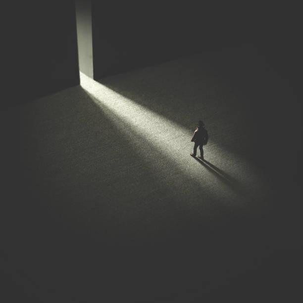 man walking in the night following light stock photo