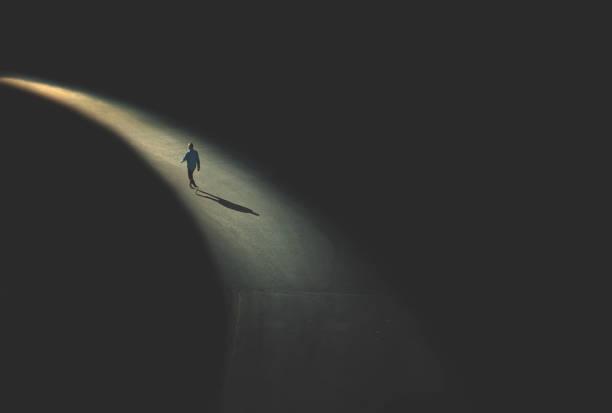 man walking in the night stock photo