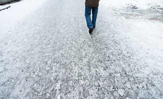 Man walking in the road covering with snow.