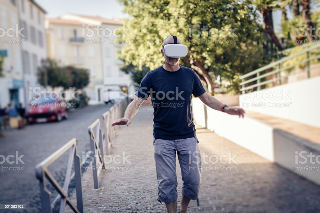 Man walking in the street wearing VR glasses stock photo