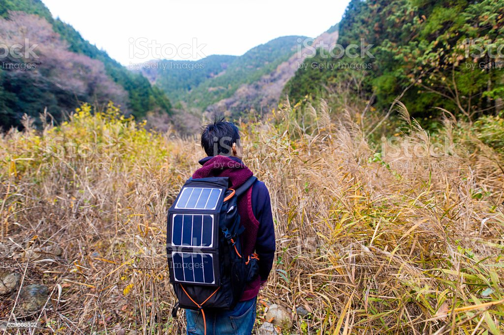 Man walking into wilderness with solar cells on his backpack stock photo