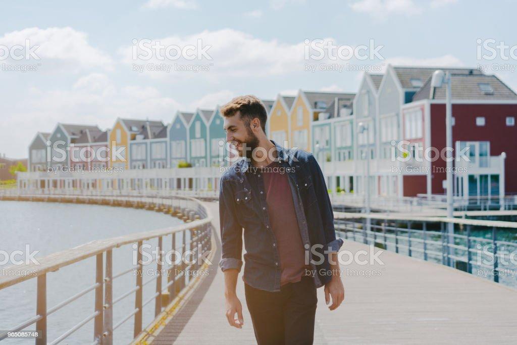 Man walking near colorful buildings near the lake zbiór zdjęć royalty-free