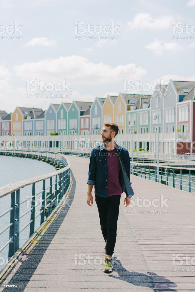 Man walking near colorful buildings near the lake royalty-free stock photo