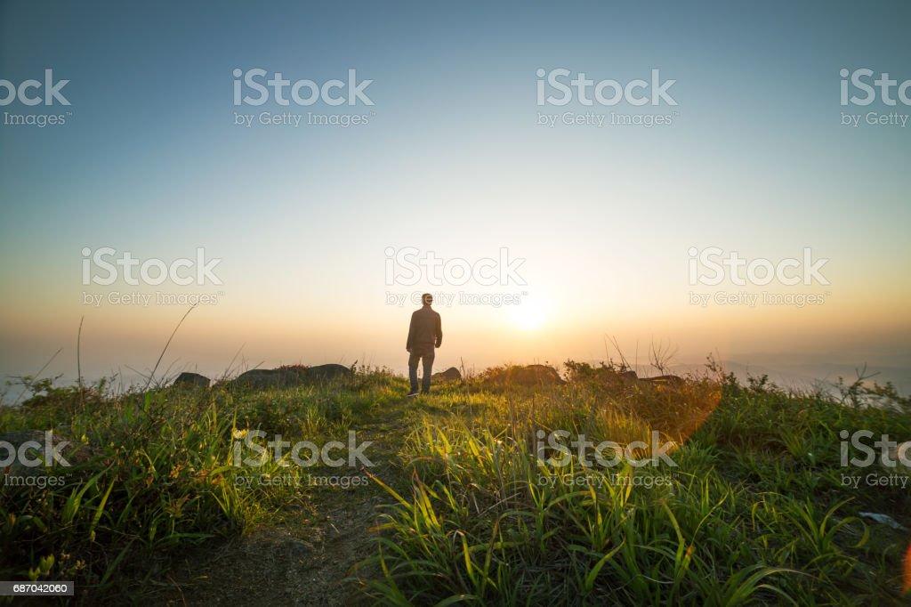 man walking near sunset on top of mountain stock photo