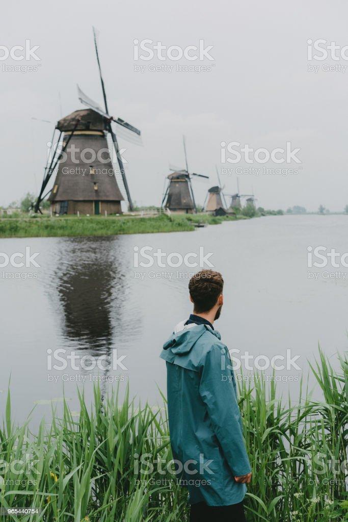 Homme qui marche près de moulins à vent aux Pays-Bas - Photo de Admirer le paysage libre de droits