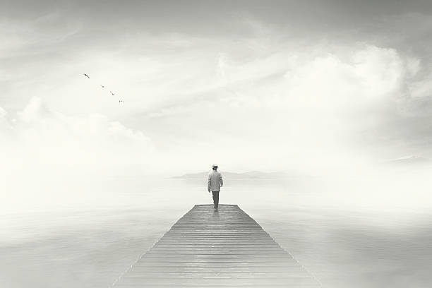 Man walking on a boardwalk in the fog stock photo