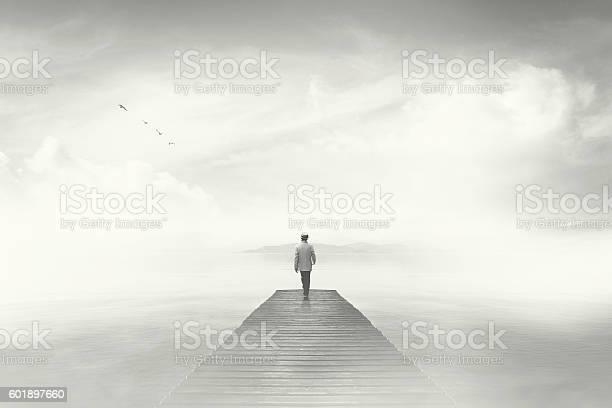Photo of Man walking on a boardwalk in the fog