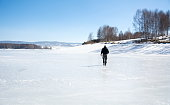 Man walking on a frozen lake surface on a winter day