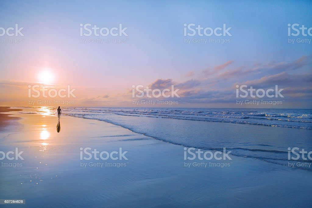 Man walking on beach at sunrise stock photo