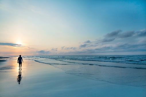 Man walking on beach at sunrise