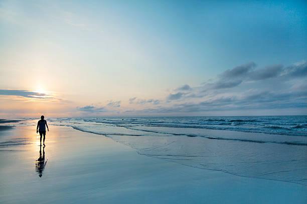 homem a caminhar na praia ao nascer do sol - water born nature imagens e fotografias de stock