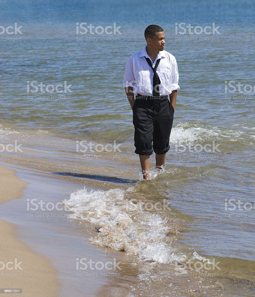 Man walking on beach with waves royalty-free stock photo