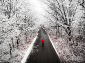 Aerial color image, taken by drone, depicting a lone man standing in the middle of an empty road, flanked on both sides by freezing white winter forest. The trees are covered with snow and ice, and the man, whom we see in rear view, is wearing a red winter jacket and knit hat. He is staring at the road ahead as it recedes into the distance.