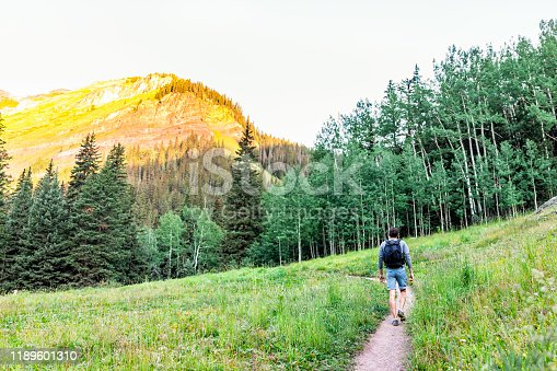 Man walking on green alpine meadow footpath trail to Ice lake near Silverton, Colorado in August 2019 summer morning and peak
