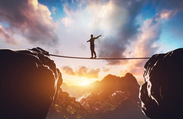 Man walking on rope between two high mountains Man walking on rope between two high mountains at sunset. Concept of taking a risk, adventure, motivation. 3d illustration balance stock pictures, royalty-free photos & images