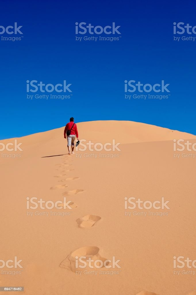 Man walking on sand dunes to the sky. stock photo