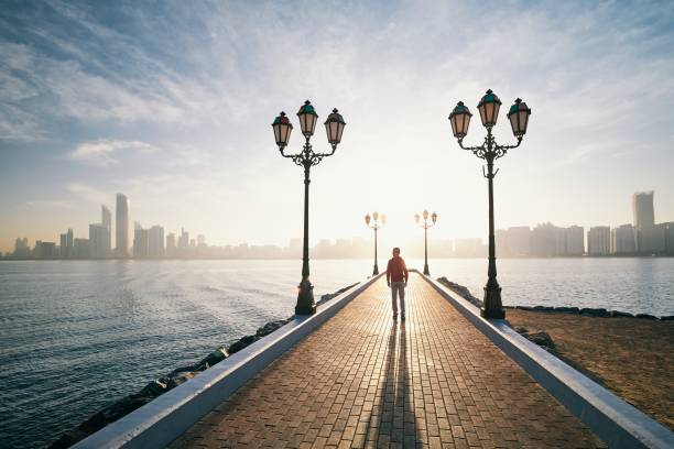 Man walking on sidewalk against urban skyline at sunrise stock photo