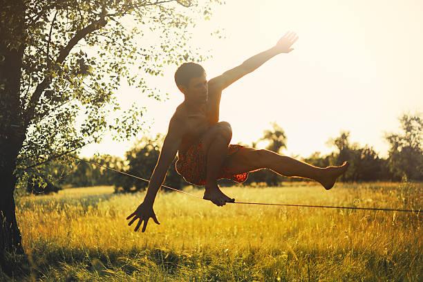 mann zu fuß auf der slackline in der wiese bei sonnenuntergang. - slackline stock-fotos und bilder