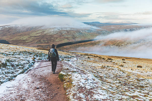 Man walking on snowy hills in winter Man walking on snowy hills in Wales. Adult man hiking in winter, hills covered in snow and mist on background. Wanderlust, nature and exploration concepts. brecon beacons stock pictures, royalty-free photos & images