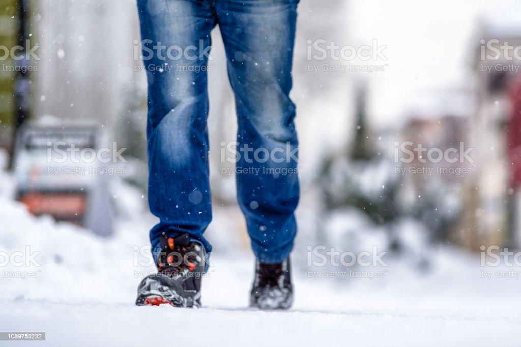 Man walking on snowy sidewalk stock photo