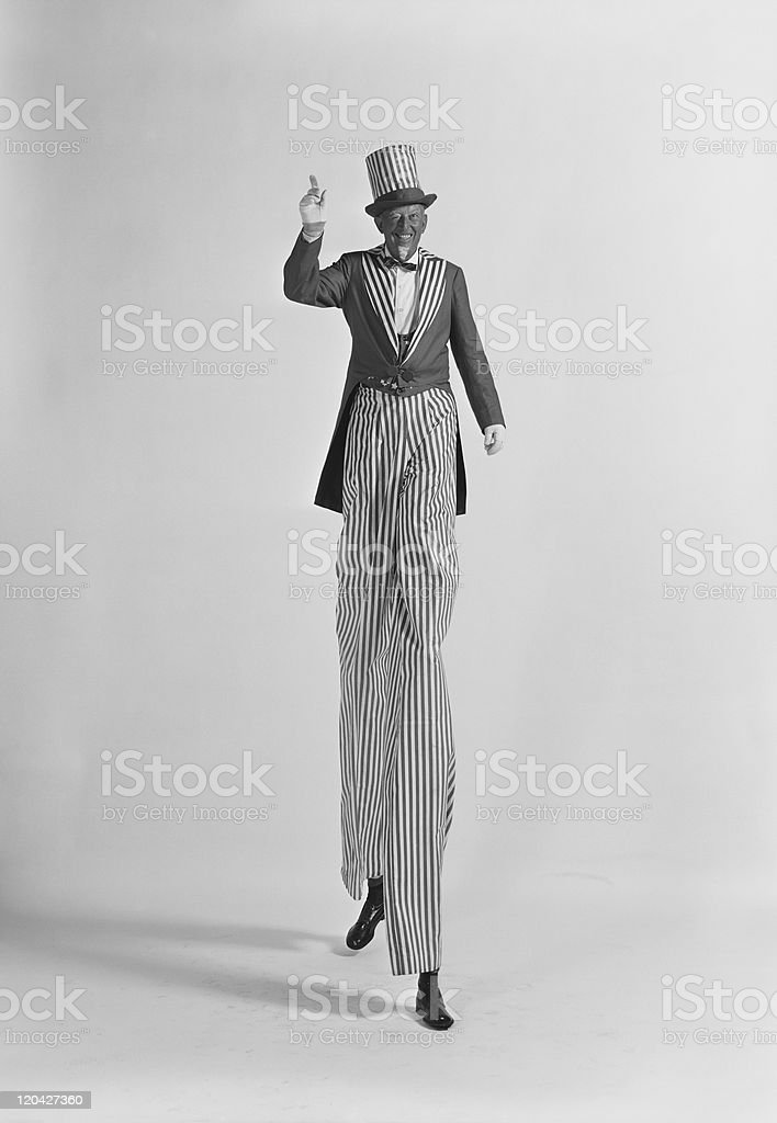 Man walking on stilts, smiling, portrait stock photo