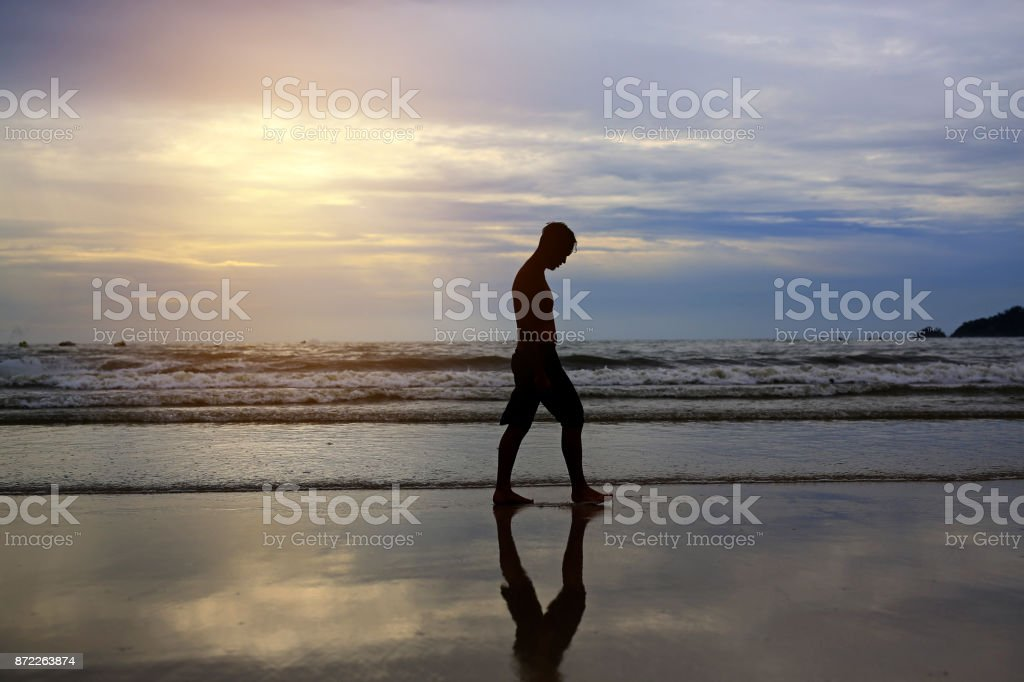 Man walking on the beach at sunset. stock photo
