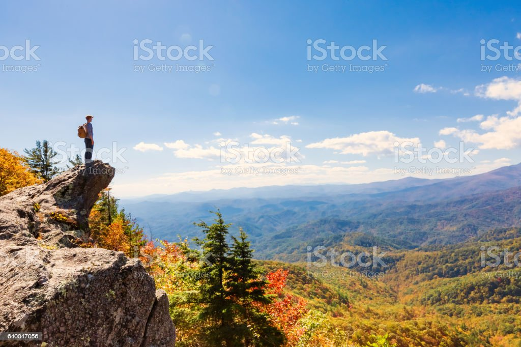 Man walking on the edge of a cliff stock photo
