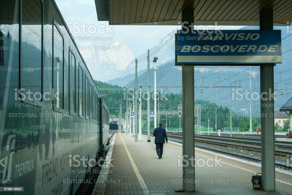 Man walking on the platform of Tariviso Boscoverde train station with an overnight train and its passenger cars waiting on the left stock photo