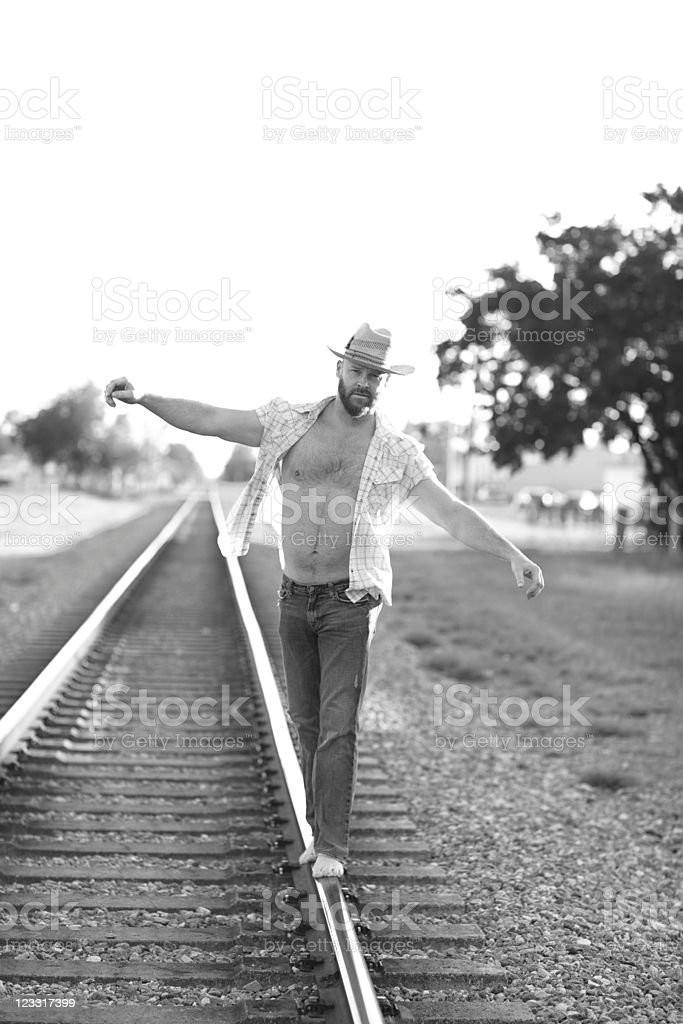 Man walking on the railroad tracks royalty-free stock photo