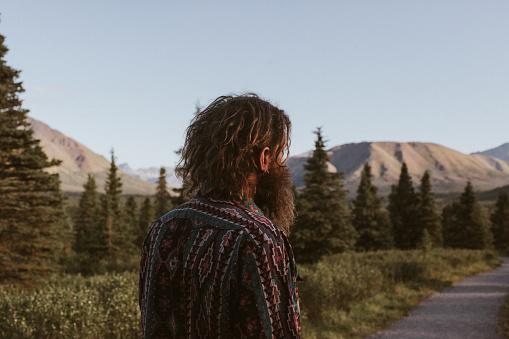 Man walks on footpath trail through Denali National Park in Alaska. It is sunset, a gentle wind blows his hair back. He has a beard.