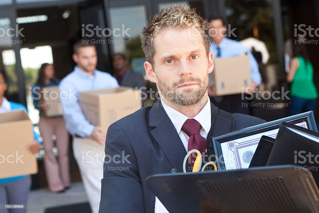 Man walking out of building with other laid off workers stock photo