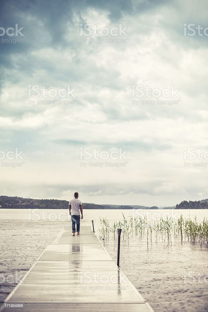 Man walking out on a pier stock photo